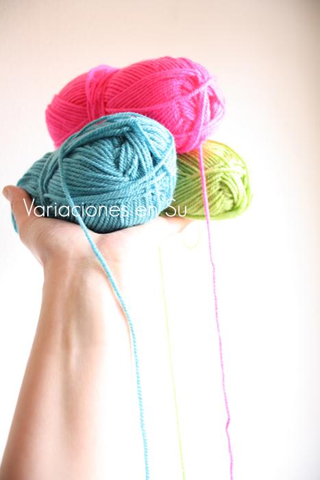 Mano sujetando ovillos de lana de varios colores.