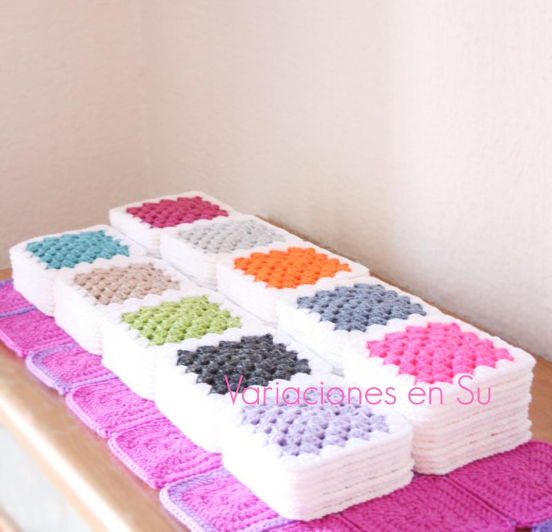 Pilas de granny squares tejidos en varios colores, para una manta de ganchillo.