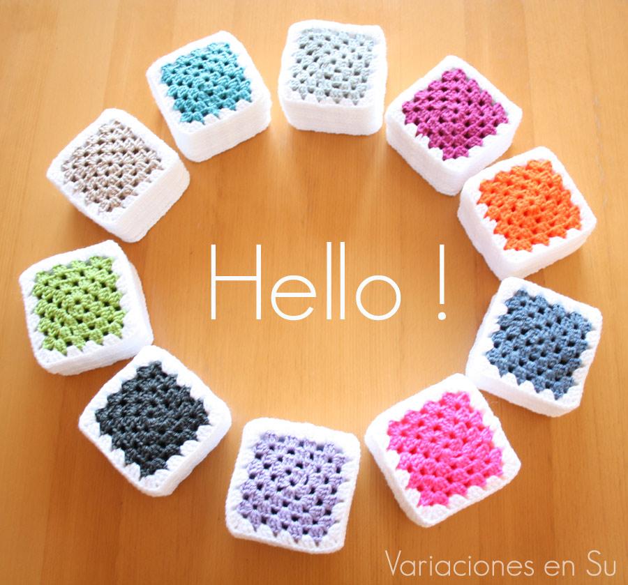Pilas de granny squares tejidos en lana de varios colores, para una manta de ganchillo.