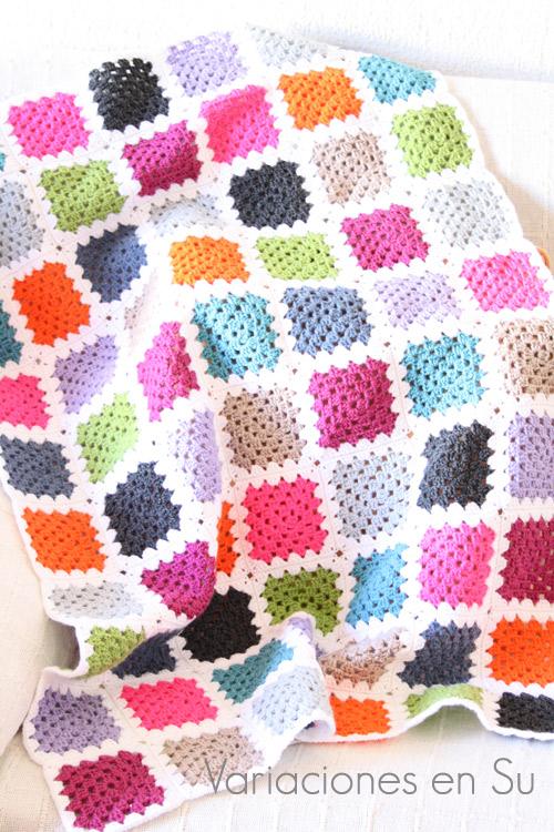 Manta formada por granny squares o cuadrados tejidos a ganchillo en proceso de elaboración.