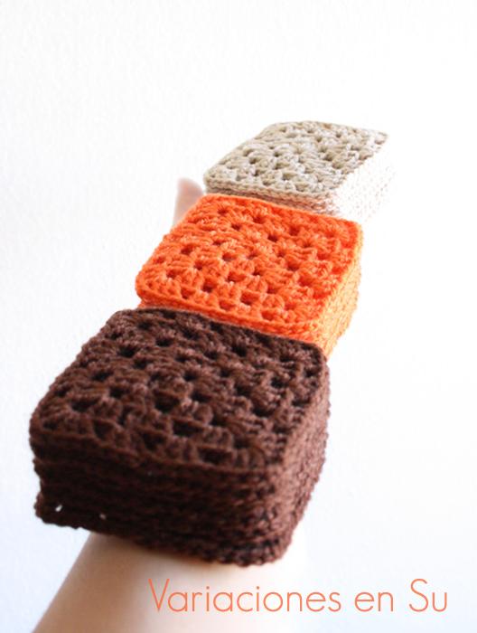 Brazo sujetando pilas de granny squares o cuadrados tejidos a ganchillo en lana de colores marrón, naranja y beige.