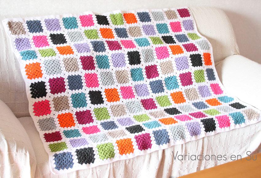 Manta de ganchillo hecha con granny squares tejidos en lana de llamativos colores.