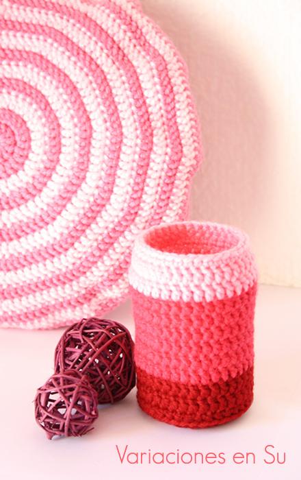 Funda de ganchillo para jarrón tejida en un degradado de tonos rosados.