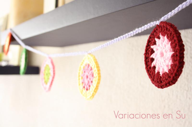 Guirnalda hecha con círculos de ganchillo tejidos en lana de alegres colores.