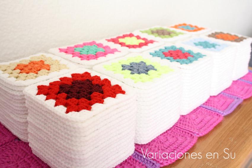 Pilas de granny squares o cuadrados de ganchillo tejidos en lana de alegres colores.