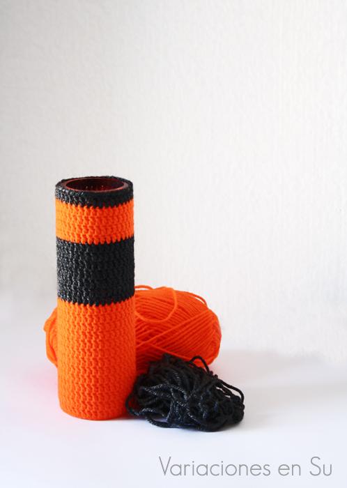 Funda de ganchillo para jarrón tejida en lana de colores naranja y gris.