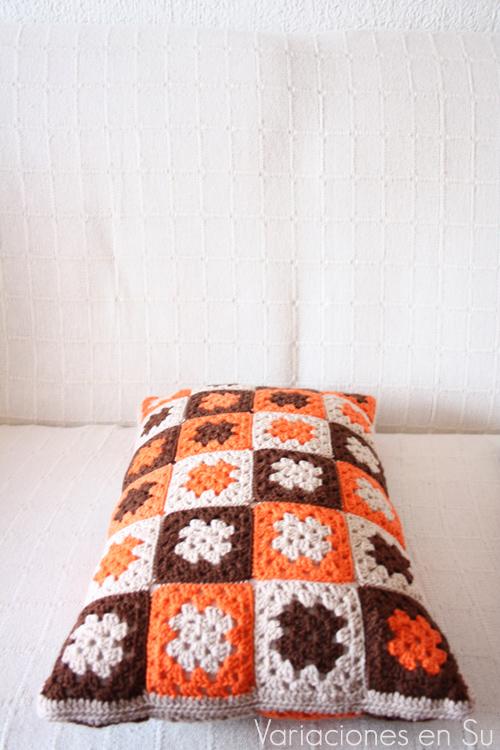 Cojín hecho con granny squares o cuadrados de ganchillo tejidos en lana de colores marrón, naranja y beige.