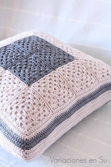 Cojín de ganchillo hecho con granny squares tejidos en los colores gris y beige.