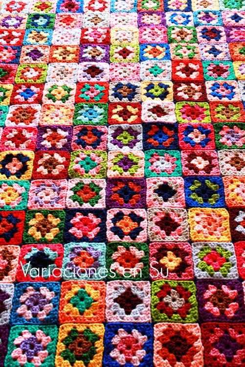 Manta de granny squares o cuadrados de punto de muchos colores, tejida a ganchillo.