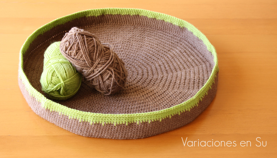 Cesta de ganchillo para gato, de forma circular y tejida en los colores marrón y verde pistacho.