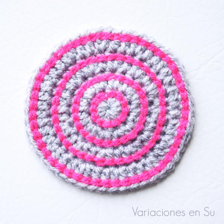 Posavasos de ganchillo, de forma circular y tejido en lana de colores gris y rosa.