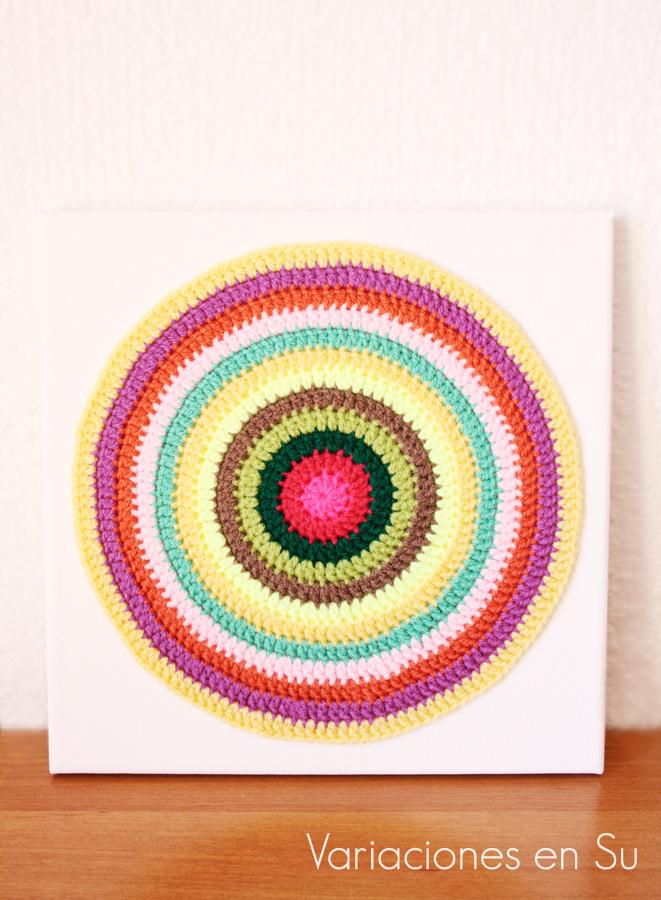 Mandala de ganchillo tejido en lana de alegres colores y enmarcado.