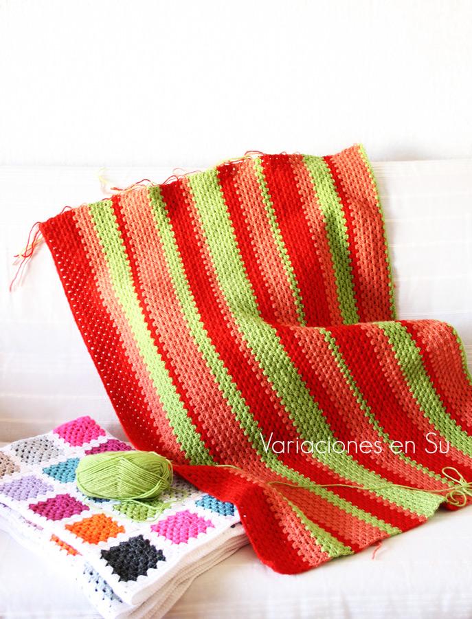 Manta de ganchillo a rayas, tejida en lana de los colores verde, naranja y rojo.