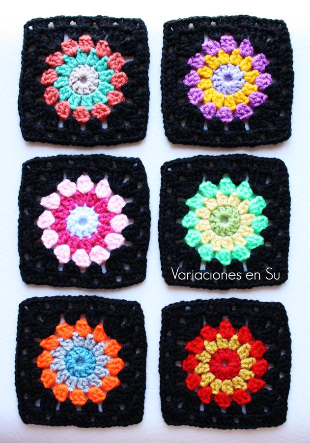 Granny squares o cuadrados de ganchillo tejidos con lana de llamativos colores combinados con negro.