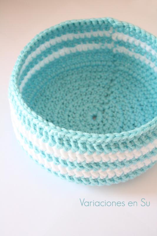 Cesta de ganchillo de forma circular tejida en colores azul y blanco.