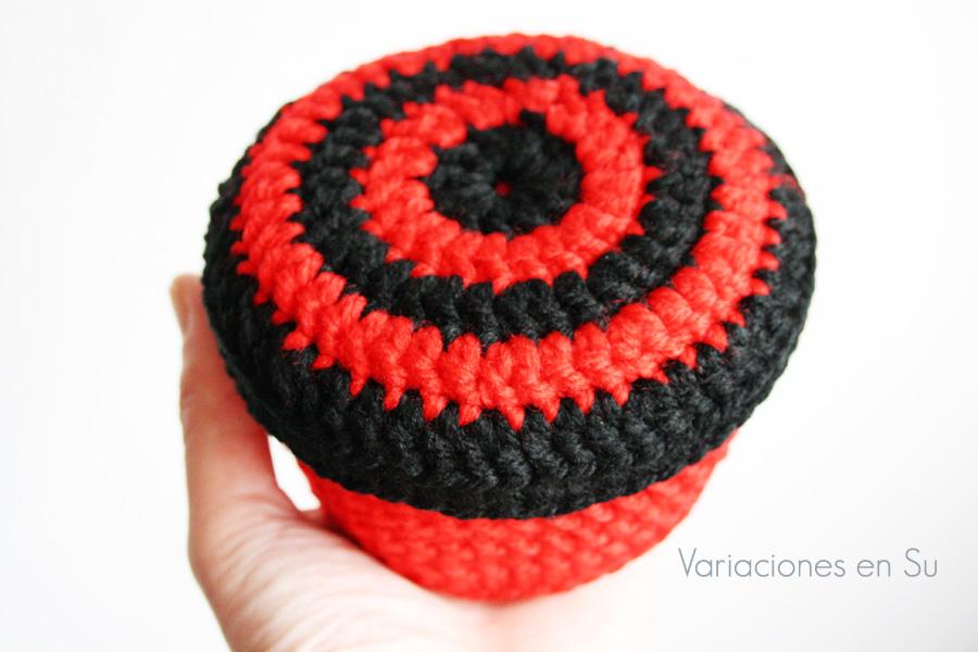 Cesta de ganchillo de forma circular tejida en los colores rojo y negro.