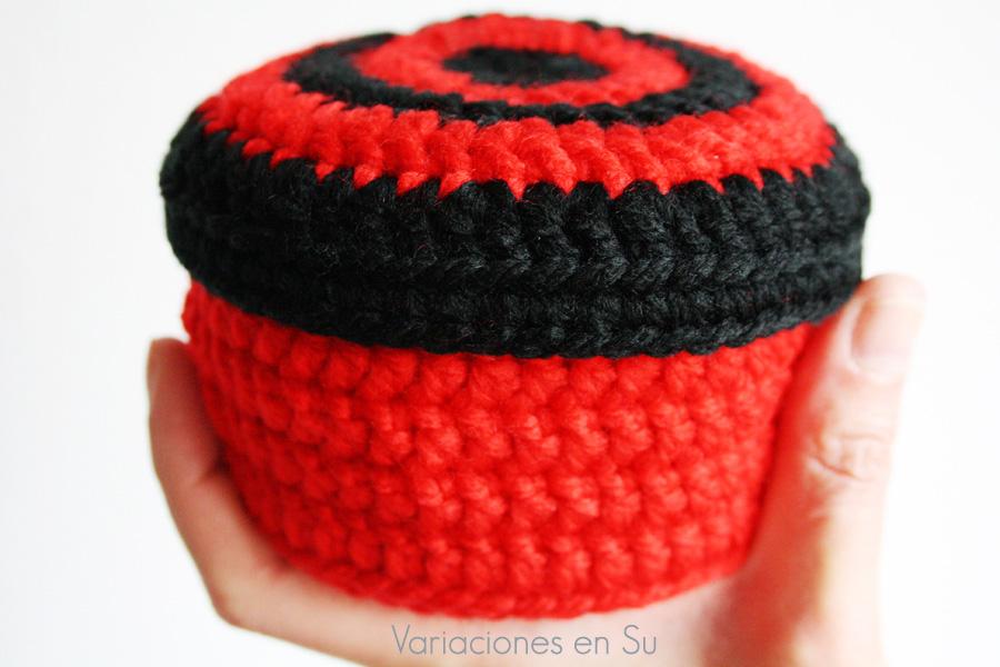 Cesta de ganchillo de forma circular con tapa incluida, tejida en los colores rojo y negro.