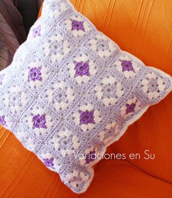Cojín de ganchillo hecho con granny squares, en colores blanco, azul y malva.