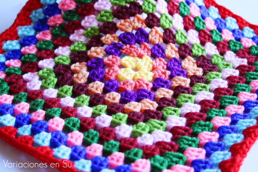 Granny square o cuadrado de ganchillo en tamaño grande, tejido en lana de varios colores.