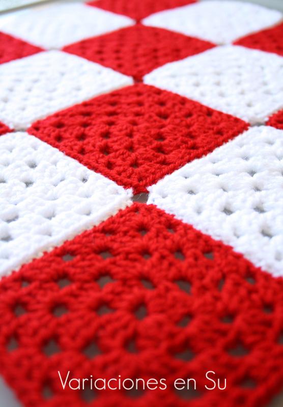 Granny squares o cuadrados de ganchillo tejidos en lana de colores rojo y blanco.
