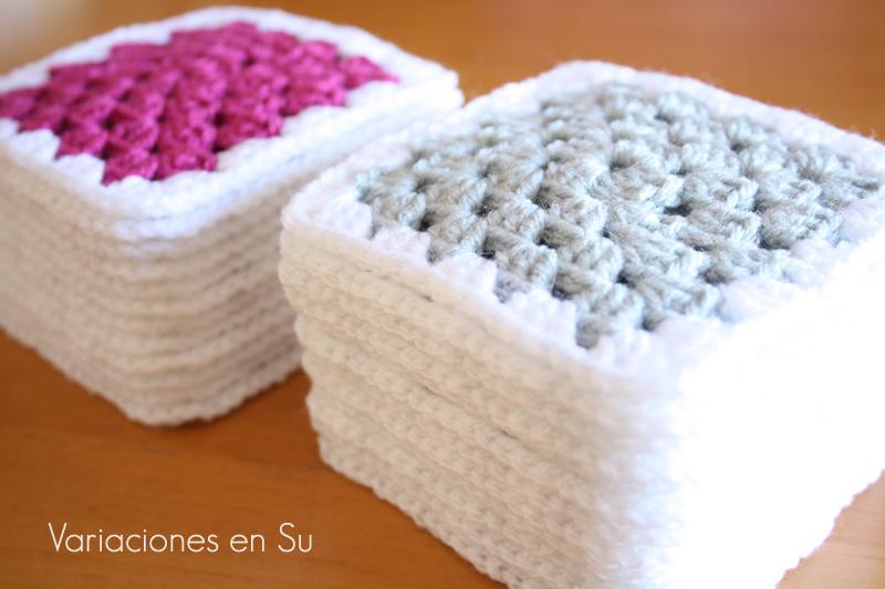 Granny squares o cuadrados de ganchillo tejidos en los colores gris perla y magenta.