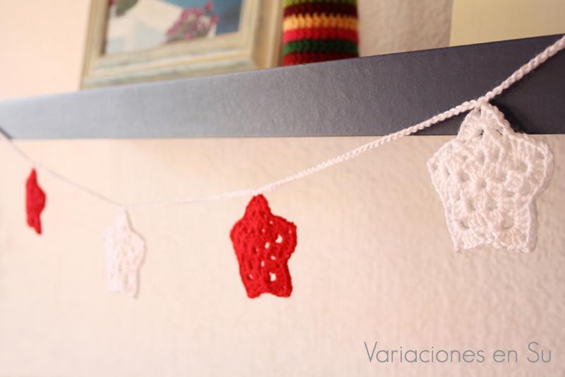 Guirnalda de ganchillo para Navidad, formada por motivos de estrella en los colores rojo y blanco.