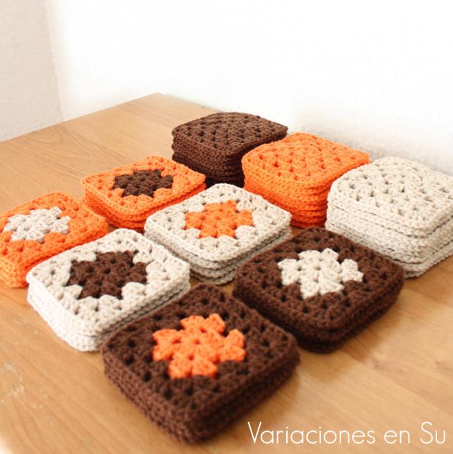 Pilas de granny squares o cuadrados de ganchillo tejidos en lana de colores marrón, naranja y beige.