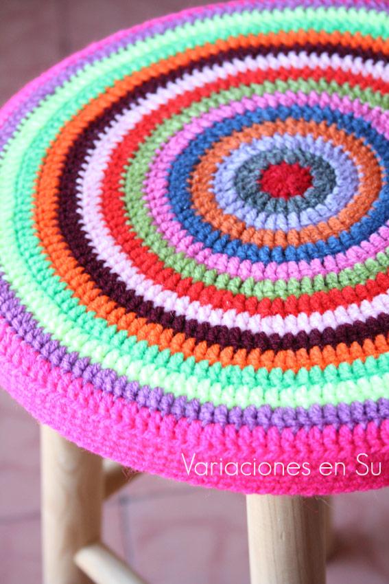Funda de ganchillo para taburete, de forma circular y tejida en llamativos colores.