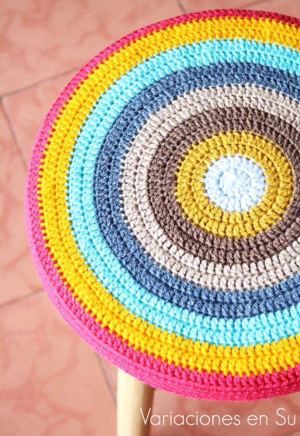 Funda de ganchillo para taburete, de forma circular y tejida en alegres colores.