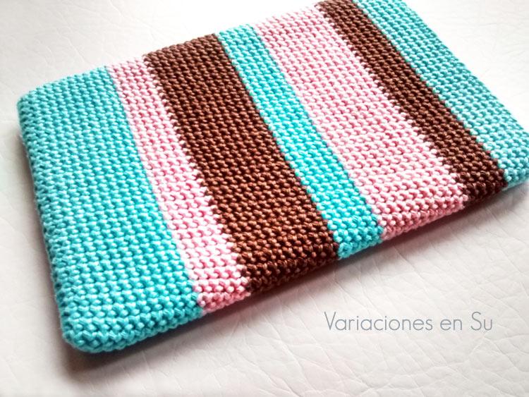 Funda de ganchillo para e-reader tejida con hilo de algodón mercerizado en los colores azul, rosa y marrón.