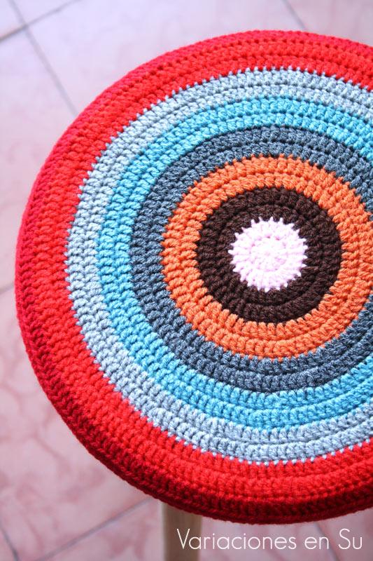 Funda de ganchillo para taburete, de forma circular y tejida en alegres colores (detalle).