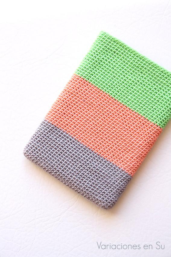 Funda de ganchillo para libro electrónico (e-reader) tejida en hilo de algodón en los colores gris, naranja y verde.