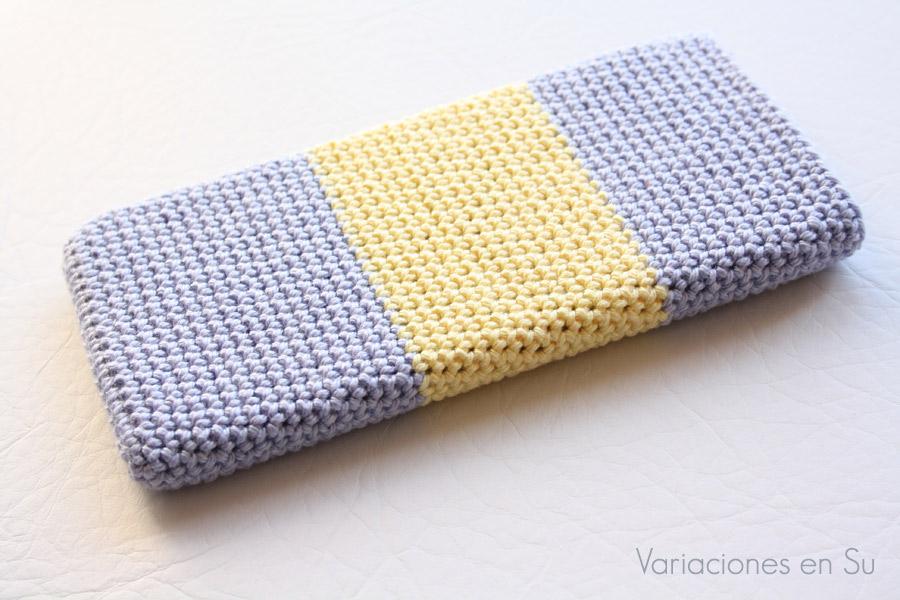 Funda de ganchillo para móvil tejida en los colores malva y amarillo.