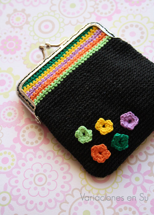 Monedero de ganchillo en negro con flores y rayas de colores, acabado con boquilla metálica plateada.
