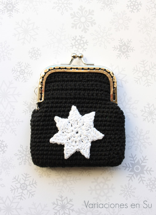 Monedero de ganchillo en color negro con figura de estrella en blanco y boquilla plateada.