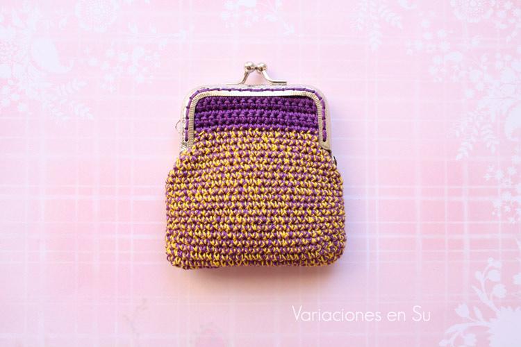 Monedero de ganchillo en violeta y amarillo, con boquilla metálica plateada.