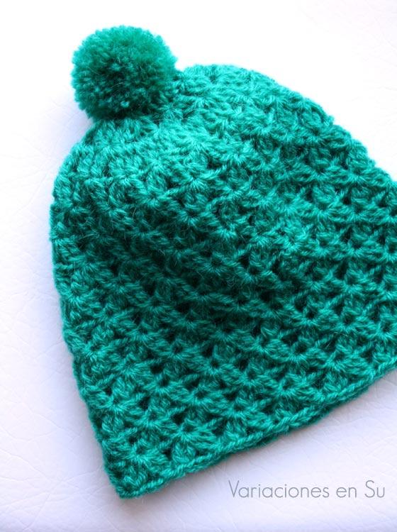 Gorro de ganchillo en color verde, con punto ligeramente calado y pompón en la parte superior.