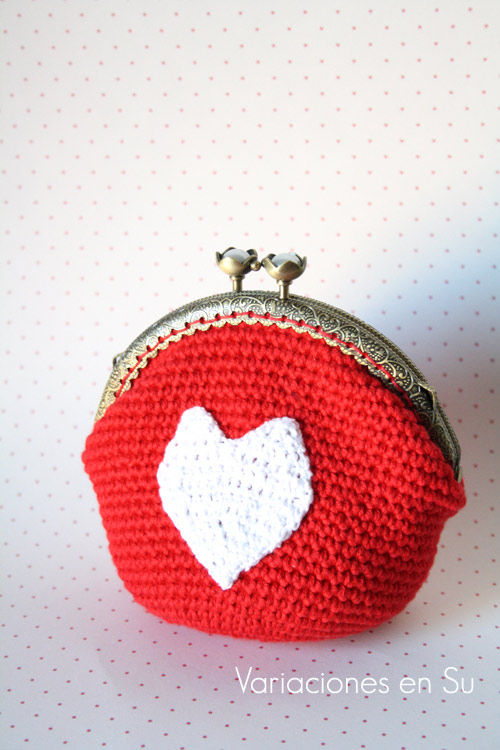 Monedero de ganchillo en rojo con figura de corazón en blanco, boquilla metálica de color bronce con filigrana y cierre en forma de flor.