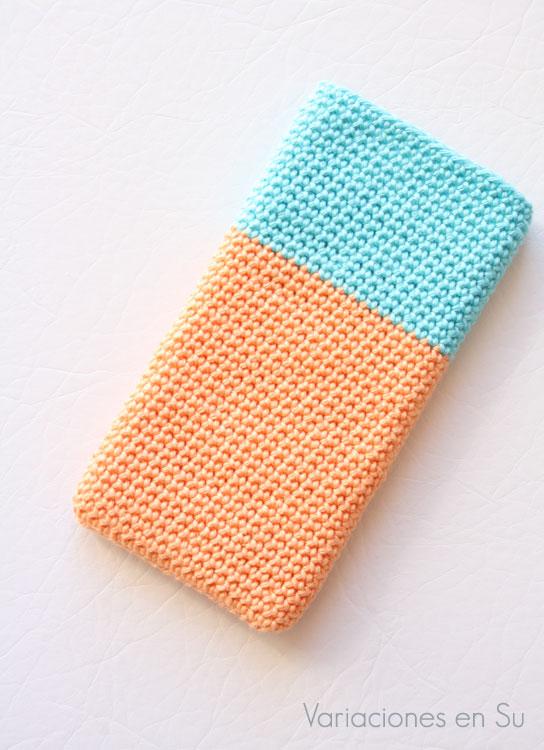 Funda para móvil tejida a ganchillo con hilo de algodón en los colores azul turquesa y salmón.