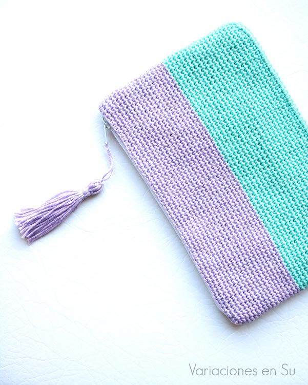 Neceser de ganchillo tejido con hilo de algodón en los colores malva y verde. Cuenta con cierre de cremallera y adorno de borla.