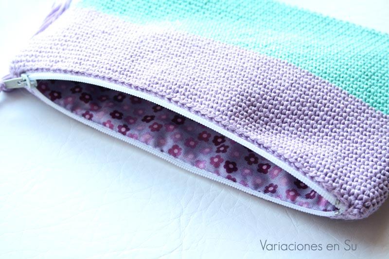 Neceser de ganchillo tejido en hilo de algodón en los colores malva y verde. Detalle del forro de la parte interior, en una bonita tela estampada.