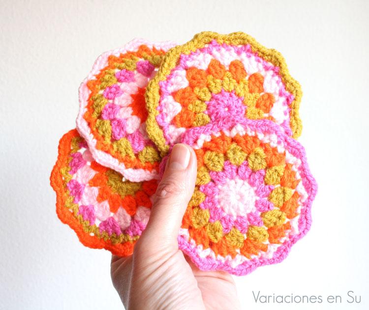Set de posavasos tejidos a ganchillo en tonos rosa, naranja flúor y amarillo mostaza.