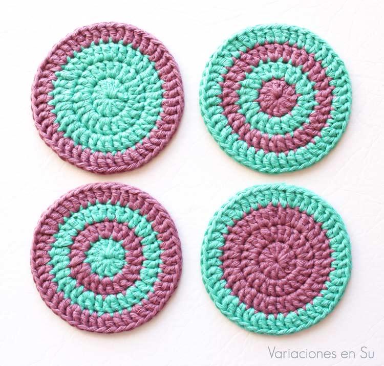 Set de cuatro posavasos de ganchillo tejidos con hilo de algodón en los colores verde y malva.