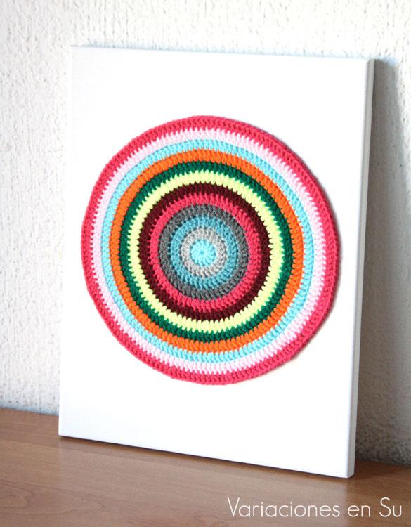 Mandala de ganchillo enmarcado, tejido en lana acrílica de alegres colores.