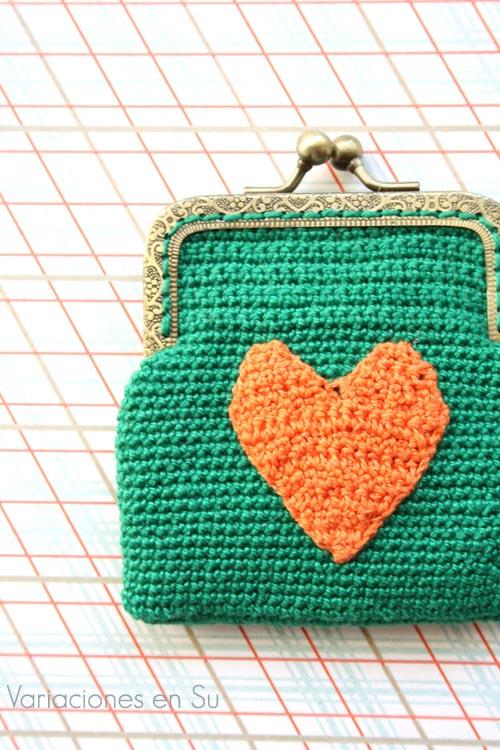 Monedero de ganchillo en color verde con figura de corazón en naranja y boquilla metálica de color bronce con filigrana.