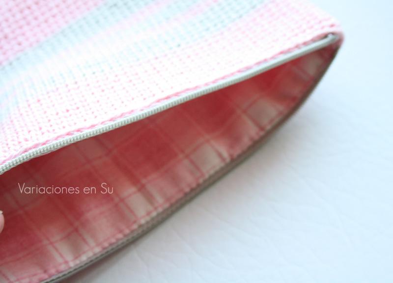 Neceser de ganchillo tejido con hilo de algodón en los colores rosa y gris. Detalle del cierre de cremallera y forro interior.