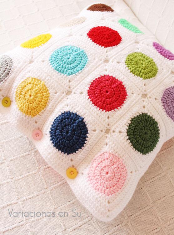 Cojín de ganchillo con círculos de llamativos colores sobre fondo blanco.
