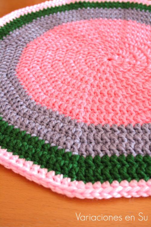 Alfombra de ganchillo de forma circular y tejida en varios colores, en proceso de realización.