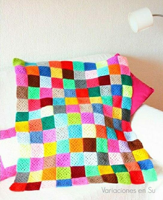 Manta de ganchillo formada por granny squares de múltiples colores, en proceso.