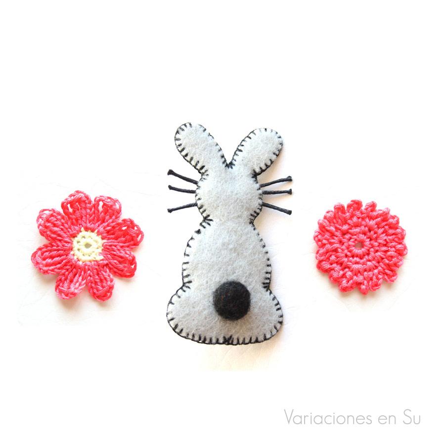Broche con forma de conejo hecho con fieltro. Flores de ganchillo.